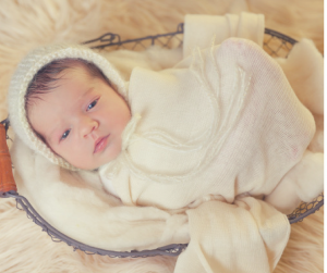 Vancouver washington baby wrapped in white and in a basket, eyes open and looking at Portland Oregon birth photographer