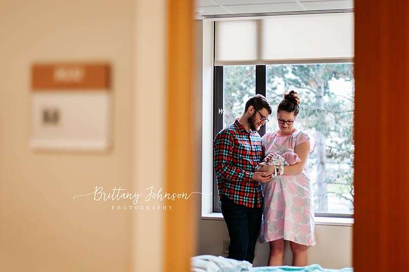 birth center childbirth options in Portland Oregon | couple by the window holding their newborn baby after a birth center birth