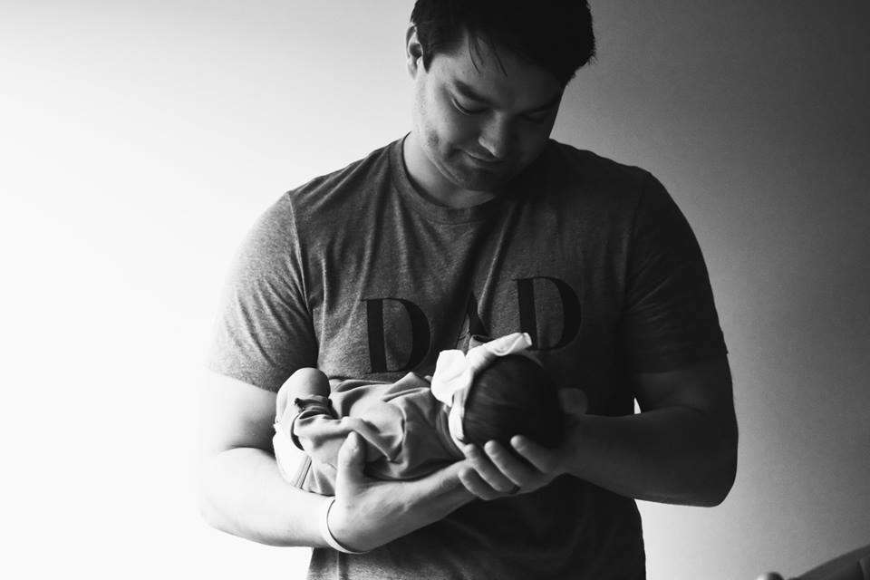 Portland oregon dad holding his newborn baby after birth wearing a shirt that says Dad